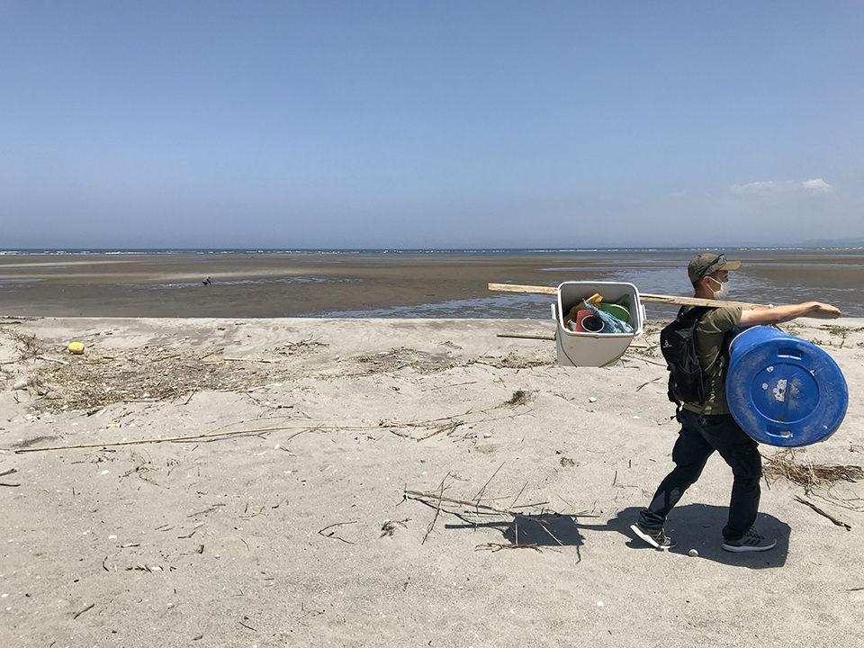 海岸で拾った全てを天秤棒で運ぶ