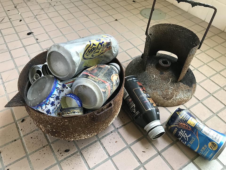 プロパンボンベから作った溶融釜にアルミ缶を入れる